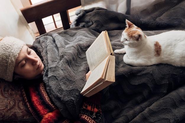 Une vraie femme aime lire un livre et passer du temps avec son chat sur le canapé à la maison par une journée froide.