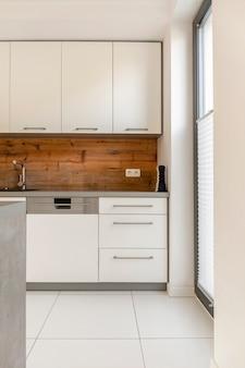 Vraie photo d'un intérieur de cuisine élégant et blanc avec des panneaux en bois au mur et des placards blancs
