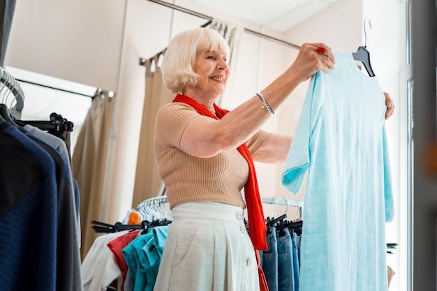 Vraiment confortable. tour de taille d'une femme âgée heureuse en admirant la robe d'été dans un magasin de vêtements tout en exprimant des émotions positives