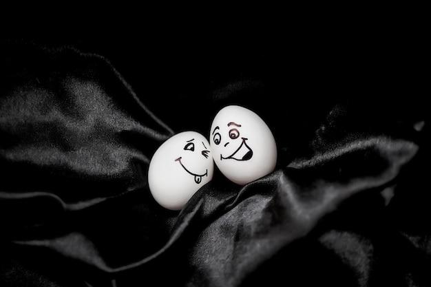 De vrais œufs peints à la main. œufs blancs aux visages dessinés disposés en carton.