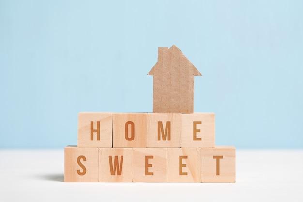 Vue abstraite d'une douce maison en carton sur un fond bleu avec l'inscription.