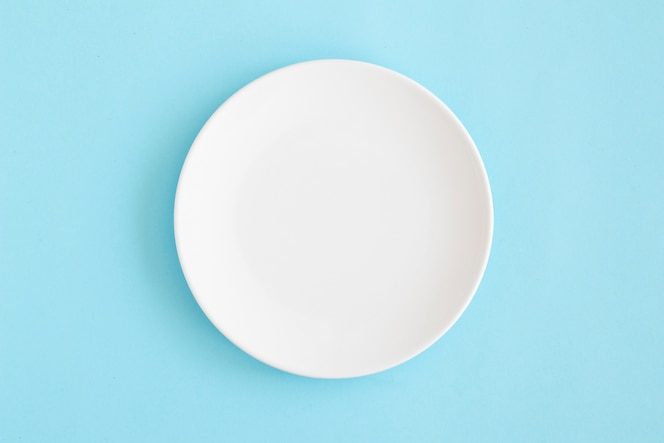Vue aérienne d'une assiette vide blanche sur fond bleu