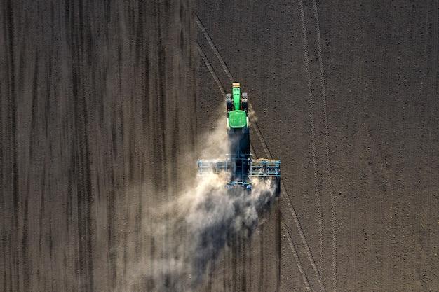 Vue aérienne de l'agriculteur dans un tracteur préparant la terre avec un cultivateur de semis
