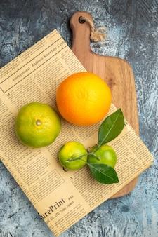 Vue aérienne d'agrumes frais avec des feuilles et du papier journal sur une planche à découper en bois coupée en deux sur une table grise