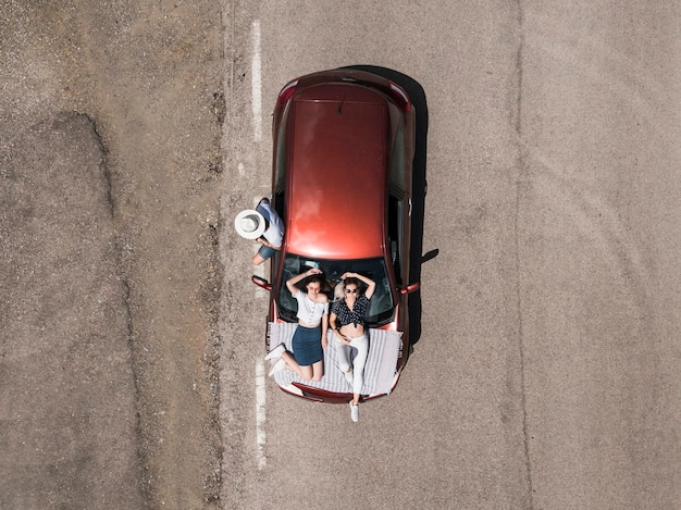 Vue aérienne des amis avec la voiture sur la route