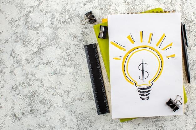Vue aérienne de l'ampoule sur les cahiers à spirale fermés et les appareils de bureau sur le côté gauche sur une surface blanche