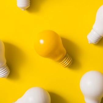 Vue aérienne de l'ampoule jaune au milieu d'ampoules blanches sur fond jaune