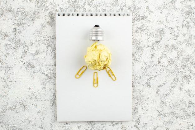 Vue aérienne de l'ampoule en papier sur un cahier à spirale fermé blanc sur une surface blanche