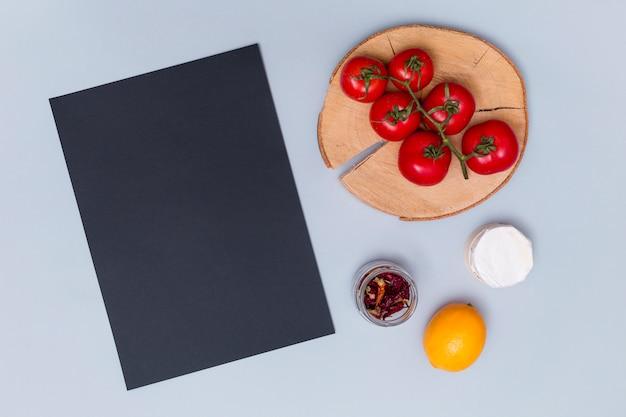 Vue aérienne d'ardoise noire avec de délicieuses tomates; piment séché; et citron