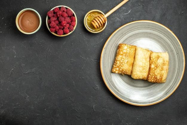 Vue aérienne de l'arrière-plan du dîner avec de délicieuses crêpes au miel et à la framboise au chocolat sur fond noir
