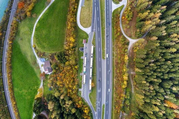 Vue aérienne de l'aube supérieure de la route de vitesse d'autoroute entre les arbres de la forêt d'automne jaune en zone rurale.