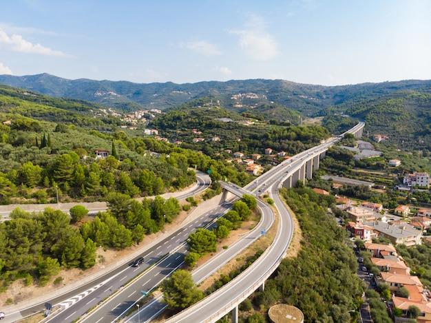 Vue aérienne d'une autoroute à plusieurs voies traversant des villages et des collines forestières