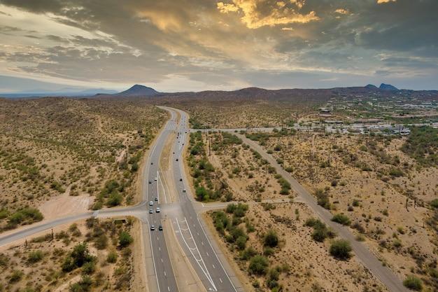 Vue aérienne de l'autoroute à travers le désert aride de l'arizona, aventure dans les montagnes, voyageant sur la route du désert près du quartier résidentiel de la petite ville de fountain hills