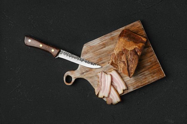 Vue aérienne de bacon de porc fumé avec du pain brun et des œufs sur une planche à découper en bois
