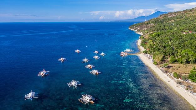 Vue aérienne de la baie et du rivage à oslob, cebu, aux philippines, c'est le meilleur endroit pour faire de la plongée avec tuba et de la plongée sous-marine et observer les requins baleines.