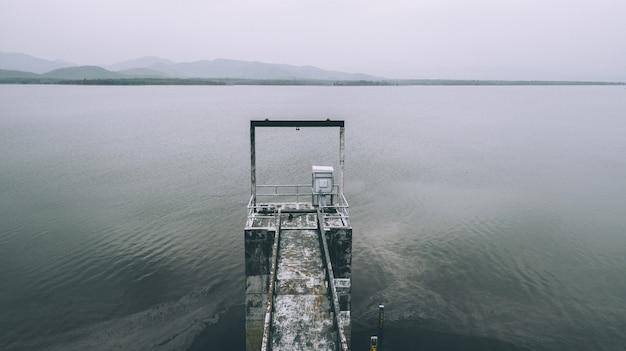 Vue aérienne de la barrière de niveau d'eau utilisée dans le petit barrage du lac pour le débit d'eau de contrôle dans le ton blanc
