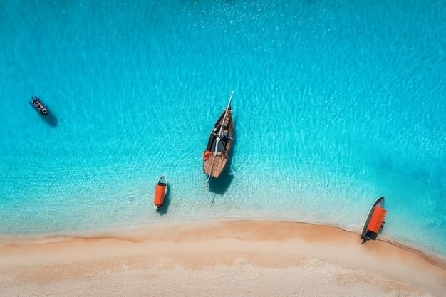 Vue aérienne des bateaux de pêche dans une eau bleu clair à une journée ensoleillée en été