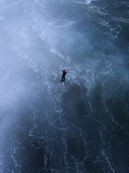 Vue aérienne d'un beau paysage marin et d'une personne nageant dans la mer sous la lumière du soleil