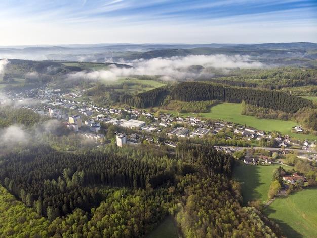 Vue aérienne de beaux champs verts et maisons de la campagne par une journée ensoleillée