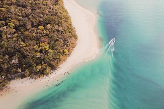 Vue aérienne de la belle mer turquoise de l'océan, bateau, plage et promenade dans la forêt d'arbres, vue de dessus du drone, concept de tourisme de vacances