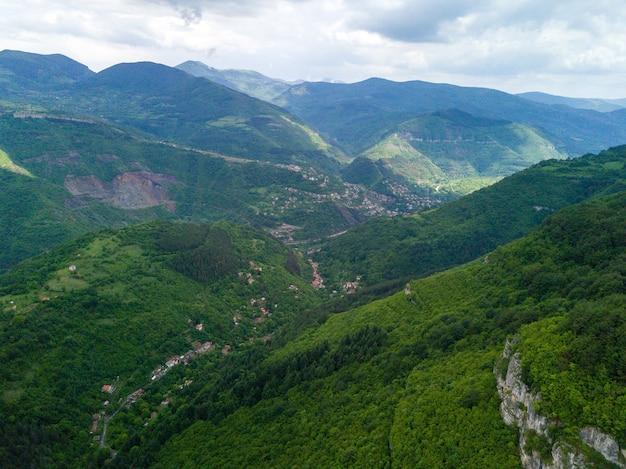 Vue aérienne des belles montagnes et vallées couvertes d'herbe et d'arbres