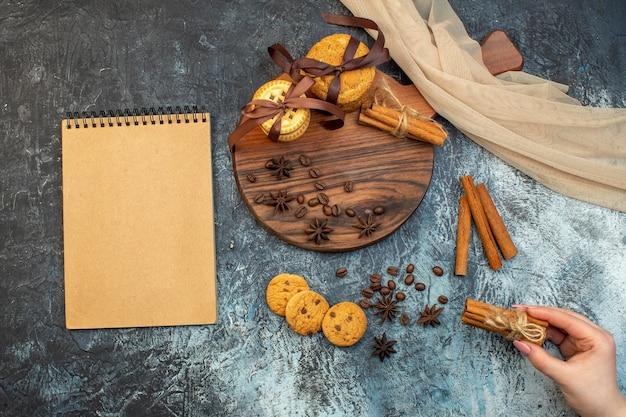 Vue aérienne de biscuits empilés limes à la cannelle sur une planche à découper en bois et un cahier de serviette nue sur fond de glace