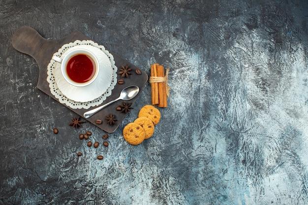 Vue aérienne de biscuits faits maison limes cannelle et une tasse de thé sur une planche à découper en bois sur fond de glace
