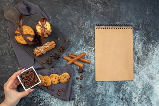 Vue aérienne de biscuits faits maison, limes à la cannelle et une tasse de thé sur une planche à découper en bois sur une serviette de couleur sombre tenant un cahier de haricots sur fond de glace