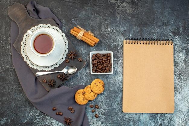 Vue aérienne de biscuits maison cannelle limes et une tasse de thé sur une planche à découper en bois cahier de grains de café sur fond de glace