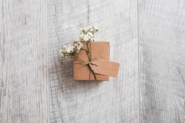 Vue aérienne d'une boîte en carton nouée avec une étiquette et des fleurs d'haleine de bébé sur un bureau en bois