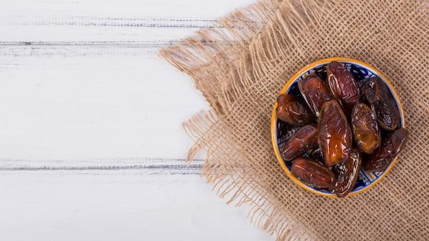 Vue aérienne d'un bol de dattes mûres juteuses sur un sac en tissu sur le bureau blanc