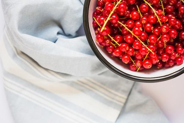 Vue aérienne d'un bol et d'une serviette de rameaux de groseilles rouges