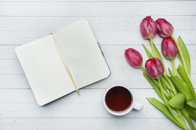 Vue aérienne d'un bouquet de tulipes et cahier et une tasse de café.