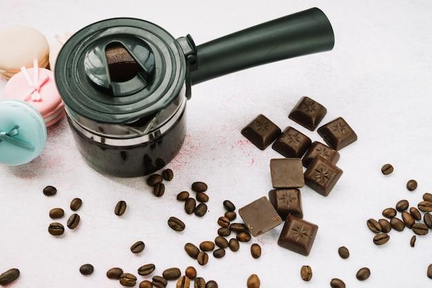 Vue aérienne d'une cafetière avec des morceaux de chocolat et des grains de café torréfiés
