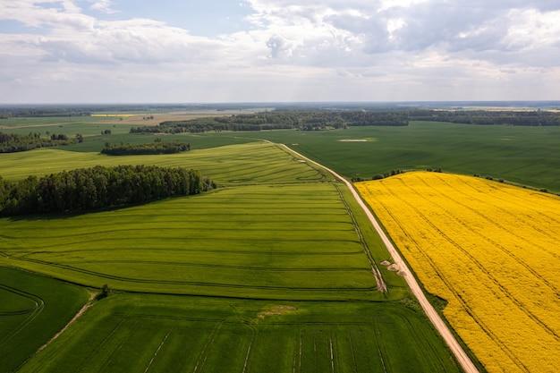 Vue aérienne de la campagne avec route, champs agricoles verts et jaunes, forêts, lettonie