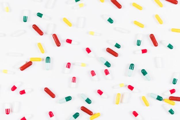 Vue aérienne de capsules colorées sur fond blanc