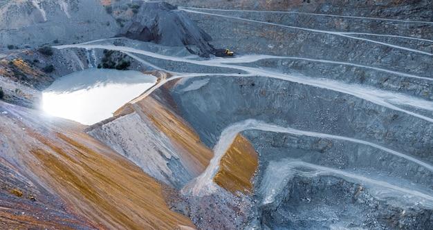 Vue aérienne sur carrière de gravier avec terrasses, bassin d'eau et concasseur de pierres