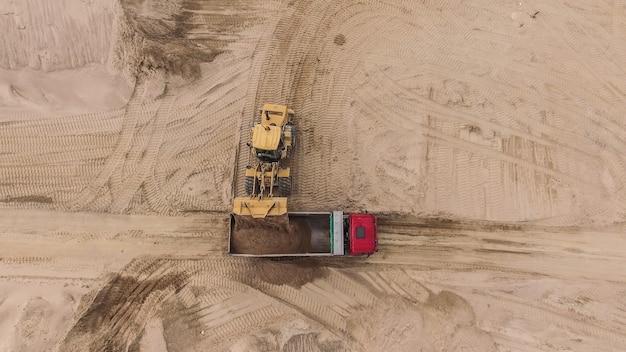 Vue aérienne de la carrière de sable avec camions et bulldozers