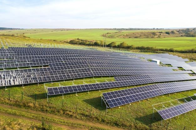 Vue aérienne de la centrale solaire en construction sur champ vert. assemblage de panneaux électriques pour la production d'énergie écologique propre.