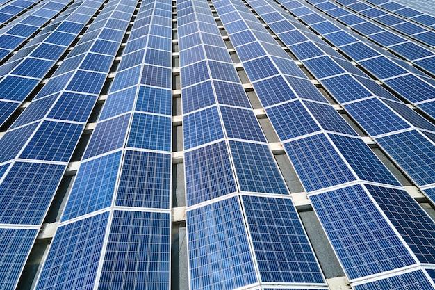 Vue aérienne de la centrale solaire avec des panneaux photovoltaïques bleus montés sur le toit d'un bâtiment industriel pour produire de l'électricité écologique verte. production de concept d'énergie durable.