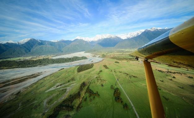 Vue aérienne sur les chaînes de montagnes et les champs verts avec l'aile d'avion franz josef nouvelle-zélande