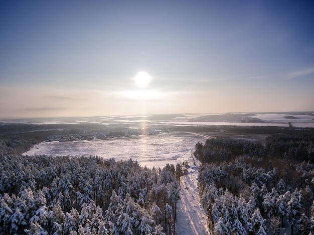 Vue aérienne sur le champ de la forêt d'hiver journée ensoleillée dans les flocons de neige sur les rayons du soleil lac et rivière