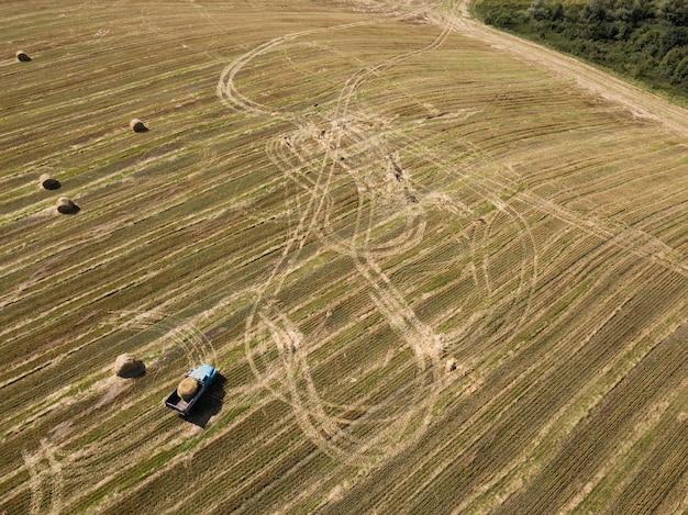 Vue aérienne d'un champ récolté avec des ballots de paille en été