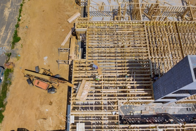 Vue aérienne de la charpente de l'appartement d'une nouvelle maison en construction avec des planches en bois d'empileur de chariot élévateur les bennes à ordures de construction
