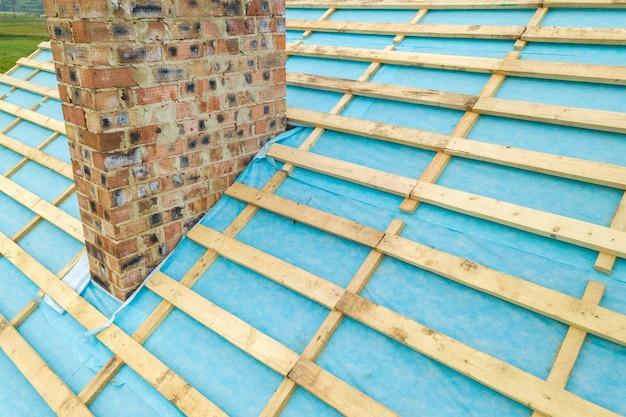 Vue aérienne d'une charpente en bois de maison en brique en construction.