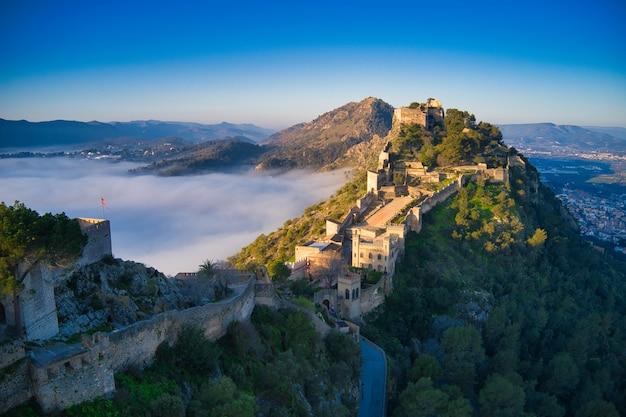 Vue aérienne d'un château médiéval sur une colline magnifiquement couverte de brouillard