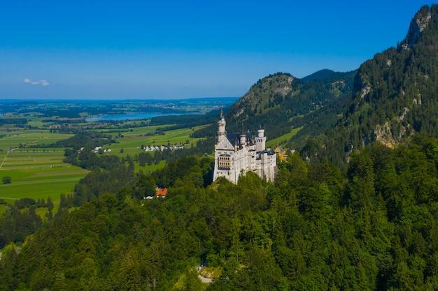 Vue aérienne sur le château de neuschwanstein schwangau, bavière, allemagne. image de drone du paysage des alpes avec des arbres et des montagnes.