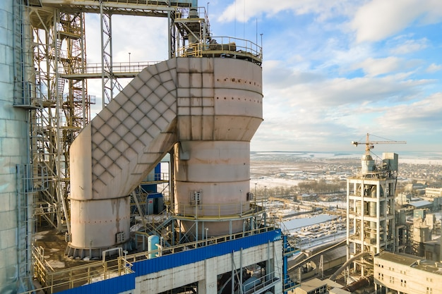 Vue aérienne de la cimenterie avec structure d'usine élevée et grue à tour dans la zone de production industrielle au coucher du soleil.