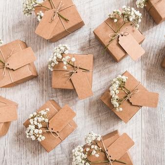 Une vue aérienne de coffrets-cadeaux de mariage avec des fleurs d'haleine de bébé sur un bureau en bois