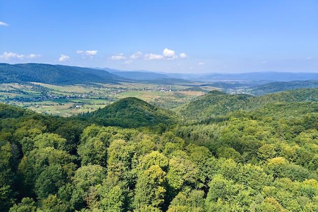 Vue aérienne de collines de montagne couvertes de bois luxuriants verts denses par une belle journée d'été.